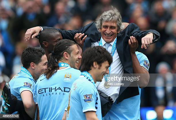 The Manchester City Manager Manuel Pellegrini is lifted up by the players to throw him in the air at the end of the Barclays Premier League match...