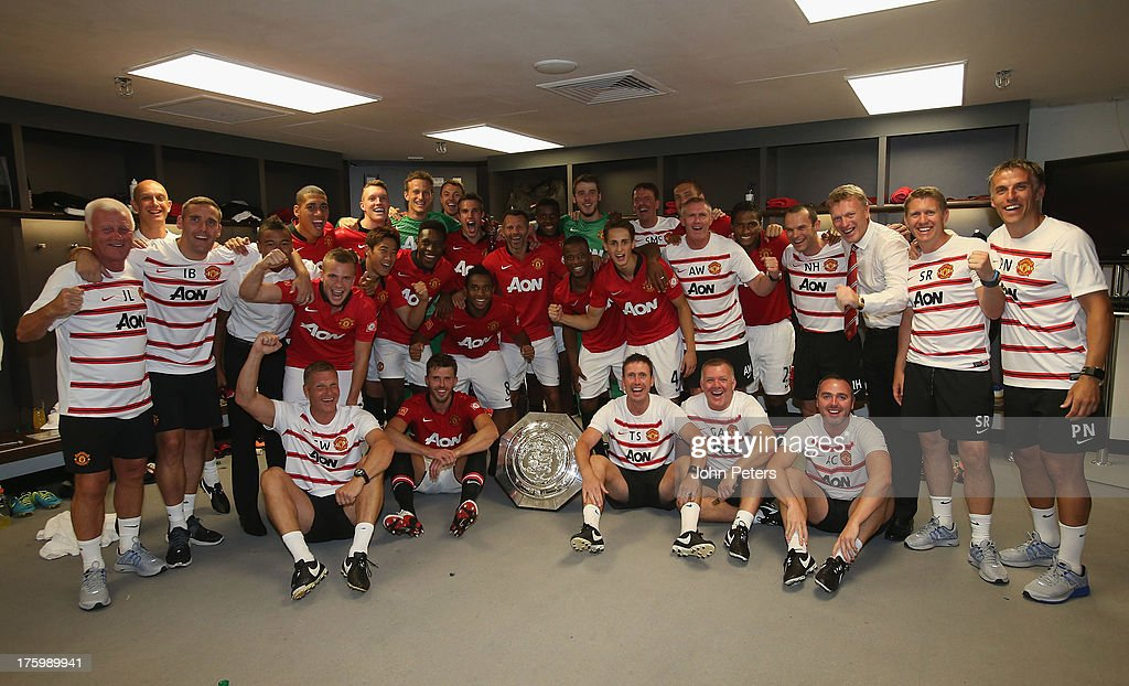 The Manchester United squad and coaching staff celebrate with the FA Community Shield trophy in the dressing room after the FA Community Shield match between Manchester United and Wigan Athletic at Wembley Stadium on August 11, 2013 in London, England.
