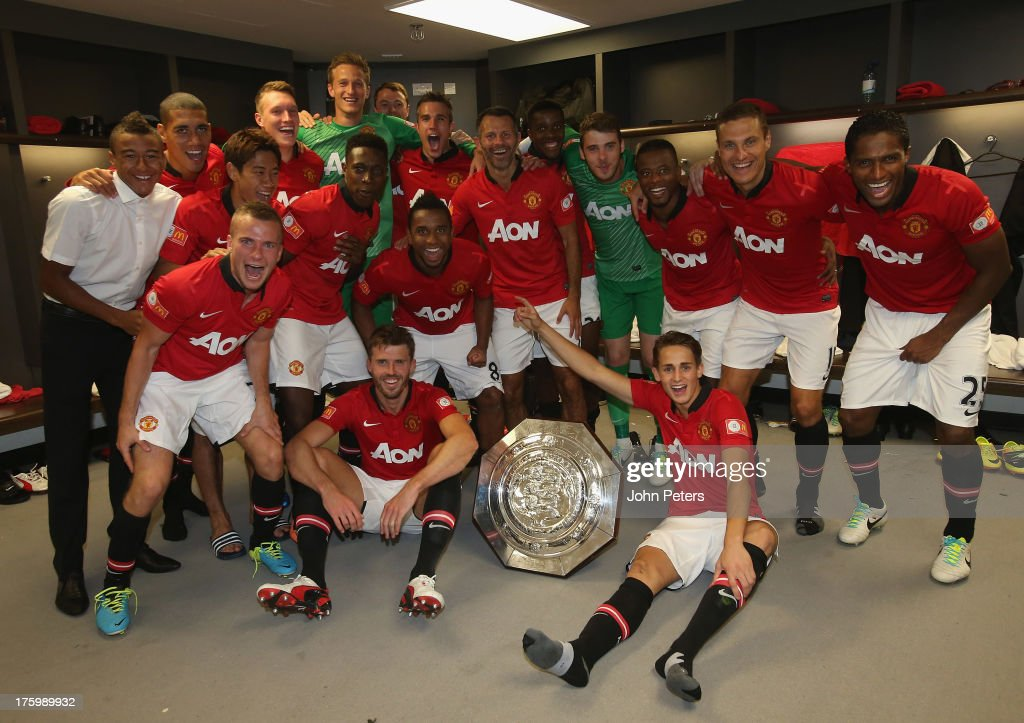 The Manchester United squad celebrate with the FA Community Shield trophy in the dressing room after the FA Community Shield match between Manchester United and Wigan Athletic at Wembley Stadium on August 11, 2013 in London, England.