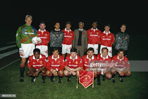 The Manchester United team lineup together for a group photograph with Nelson Mandela before a friendly match on July 28 1993 in Johannesburg South...