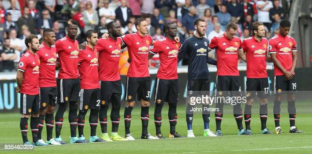 The Manchester United team take part in a minute's silence ahead of the Premier League match between Swansea City and Manchester United at Liberty...