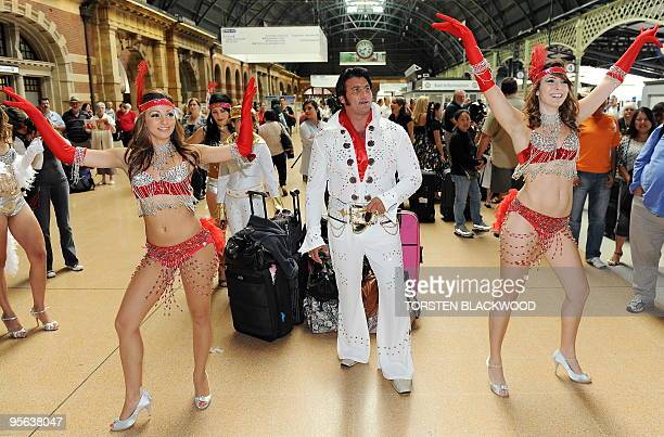 The Mancini family of Elvis and Priscilla Presley impersonators dance their way to catch the 'Elvis Express' at Central Station in Sydney on January...