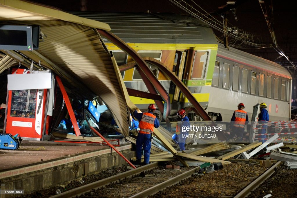 The mangled platform roof and derailed train cars are pictured at the site of a train accident on the evening of July 12, 2013 at the railway station of Bretigny-sur-Orge, near Paris. At least six people were killed and dozens injured on Friday after a speeding train derailed at a station in the southern suburbs of Paris, officials said. AFP PHOTO / MARTIN BUREAU