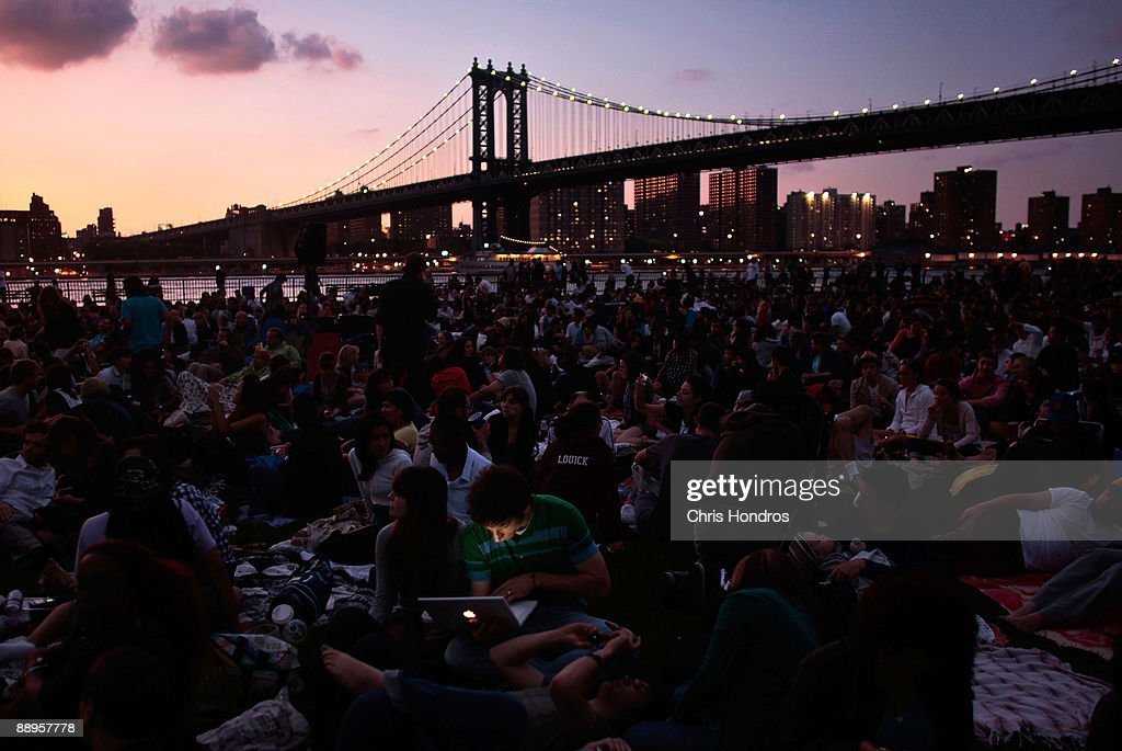 The Manhattan Bridge looms behind an audience of hundreds sitting in the grass of Brooklyn Bridge Park before the 'Movies With a View' outdoor...