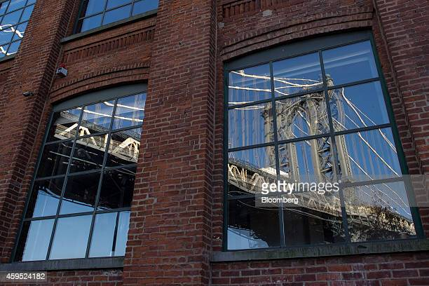 The Manhattan Bridge reflected in the window of a building on Plymouth Street in the DUMBO neighborhood in the Brooklyn borough of New York US on...