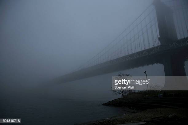 The Manhattan Bridge sits in morning fog on December 14 2015 in New York City Temperatures across much of the New York metropolitan area continued to...