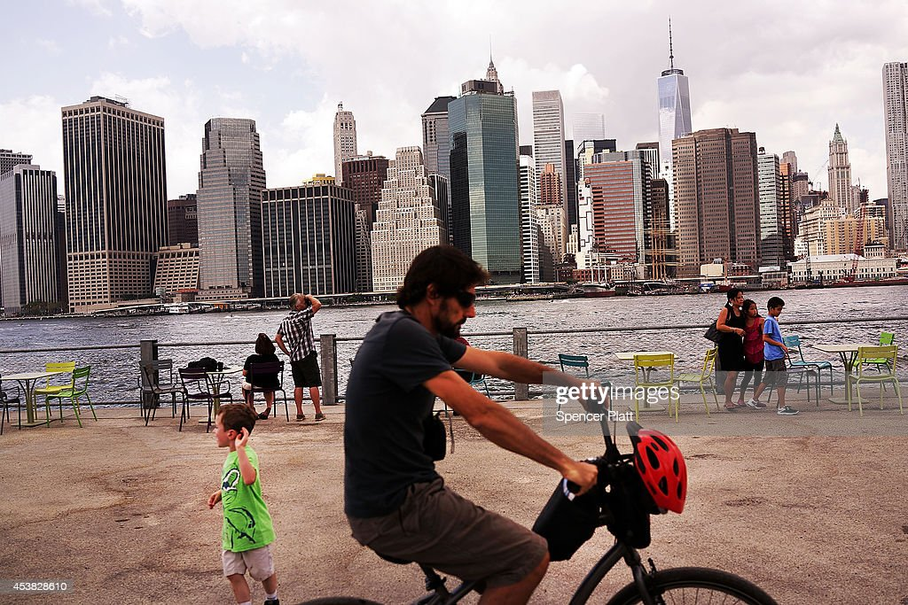 The Manhattan skyline is seen in the background as people relax in the Brooklyn Bridge Park on August 19 2014 in the Brooklyn borough of New York...