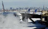 The Manhattan skyline is visible behind blowing snow around a British Airways aircraft following a major blizzard at Newark Liberty International...