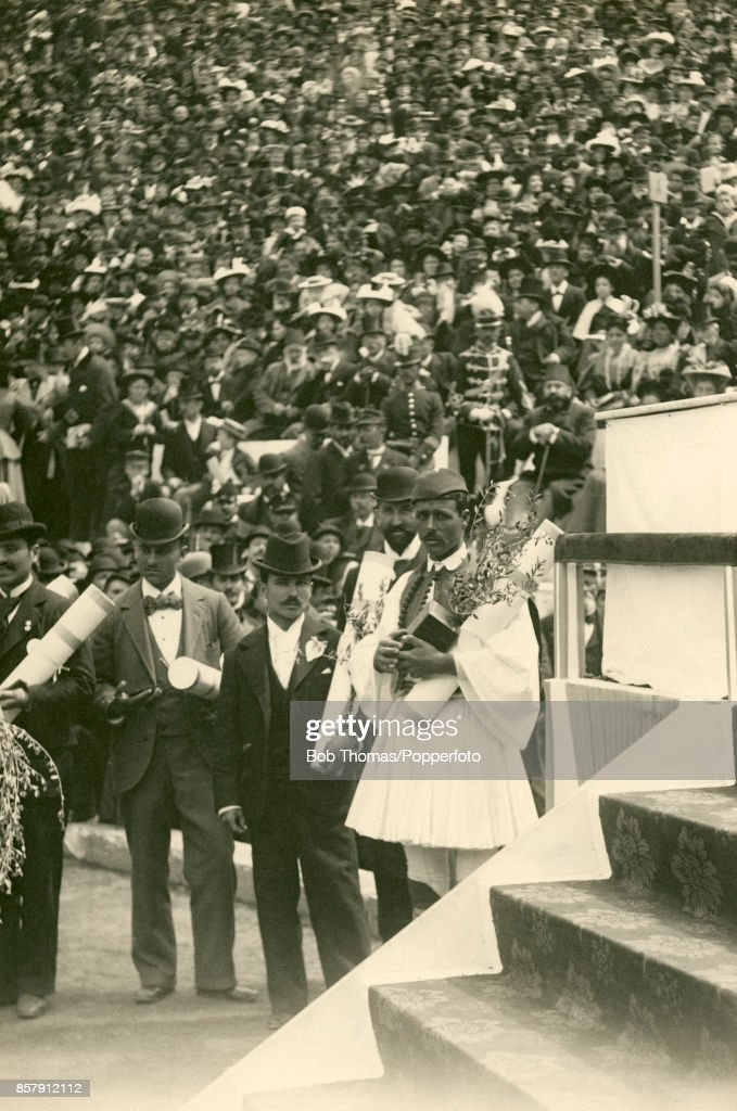 The marathon winner Spiridon Louis (right, in a fustanella, the Greek national costume), stands with his medal, an olive branch and, left to right, other prize-winning Greek Olympians - Nikolaos Andriakopoulos (gymnastics), Pantelis Karasevdas (shooting) and Leonidas Pyrgos (fencing) - before a huge crowd of enthusiastic spectators at the close of the first Modern Olympic Games in the Panathenaic Stadium in Athens on 15th April 1896. Following his victory, Louis, a water-carrier by trade, was offered any gift he wished from King George I and his request for a donkey-driven cart to help him in his business was granted. The original second and third place finishers in the event were also Greeks but, when it was discovered that one of them had covered part of the course by carriage, his place was taken by Gyula Kellner of Hungary. Despite the fact that these first Olympic Games could not be termed truly international since only 14 nations were represented - and not by national teams, but only by athletic associations, university teams and individuals, the great success of the first Games in Athens was owed to the tenacity of Pierre de Coubertin of France, known as the 'father of the Olympics' who had worked tirelessly over a number of years to garner interest and support for reviving the Games of ancient Greece, to the generosity of several wealthy Greek philanthropists, to the IOC's first president, Demetrios Vikelas, and to the enthusiasm of both the royal family of Greece and its citizenry who whole-heartedly embraced the event which has now become one of the biggest international sporting events in the world today.
