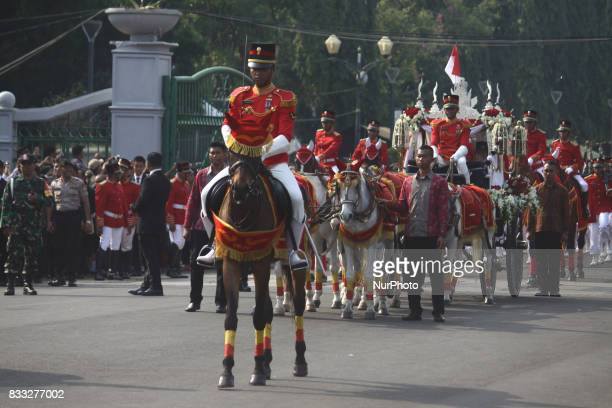 The marching band team from Indonesian military and police along with people with traditional dresses escorted the horse cart carriying the Bendera...