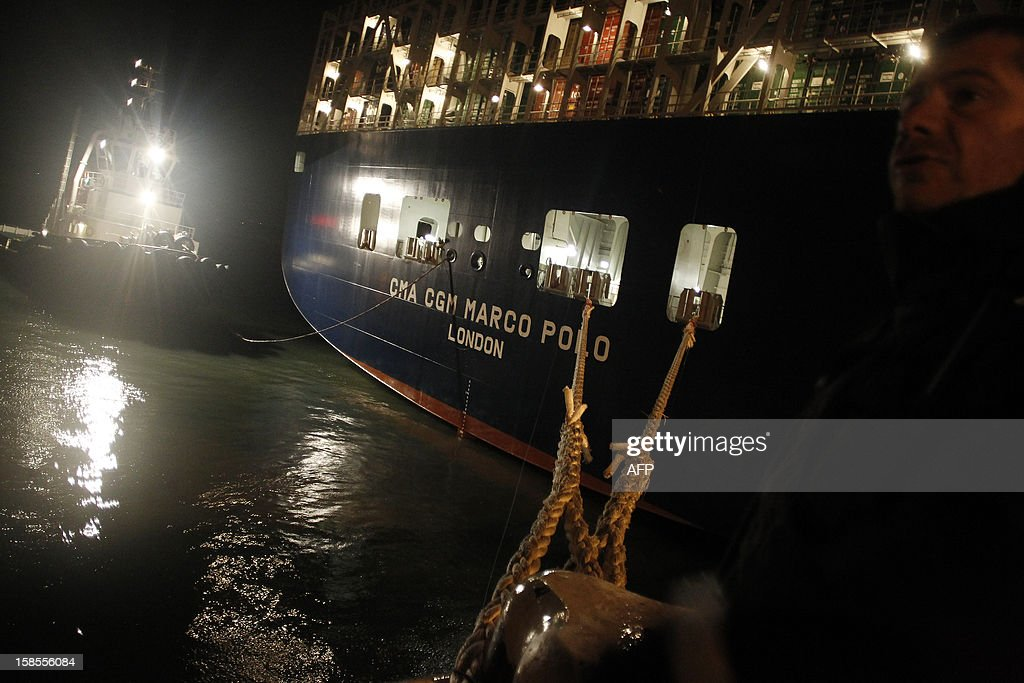 The Marco Polo, flying a British flag and said to be the world's biggest container ship by French owners CMA CGM, is towed into the port of Le Havre, western France, early on December 19, 2012. The Marco Polo was given its champagne christening in the Belgian port of Zeebrugge on December 18, 2012. The ship, which is 396 metres (yards) long -- the length of four football fields -- was built in South Korea and was to head back to Asia after a stop in France. It is said to be the largest container in the world measured by capacity, as it can hold 16,020 TEU (twenty-foot equivalent unit containers) -- or 97 kilometres of containers lined up one by one. AFP PHOTO/CHARLY TRIBALLEAU.