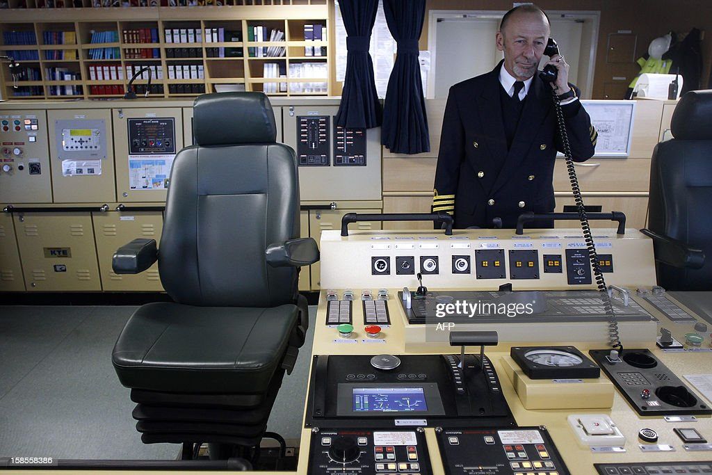 The Marco Polo's captain Igor Sikic uses a phone in the cabin control of the Marco Polo, flying a British flag and said to be the world's biggest container ship by French owners CMA CGM, moored in the port of Le Havre, western France, early on December 19, 2012. The Marco Polo was given its champagne christening in the Belgian port of Zeebrugge on December 18, 2012. The ship, which is 396 metres (yards) long -- the length of four football fields -- was built in South Korea and was to head back to Asia after a stop in France. It is said to be the largest container in the world measured by capacity, as it can hold 16,020 TEU (twenty-foot equivalent unit containers) -- or 97 kilometres of containers lined up one by one.