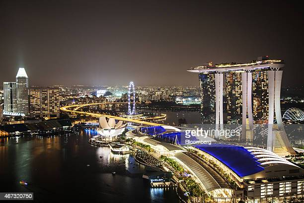 The Marina Bay Sands hotel and casino right and the Singapore Flyer center stand at night in Singapore on Sunday March 22 2015 Lee Kuan Yew who...