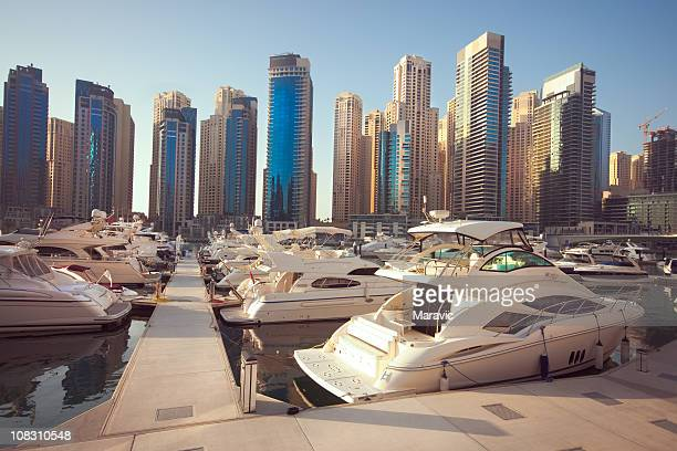 The marina in Dubai with white boats over tall buildings