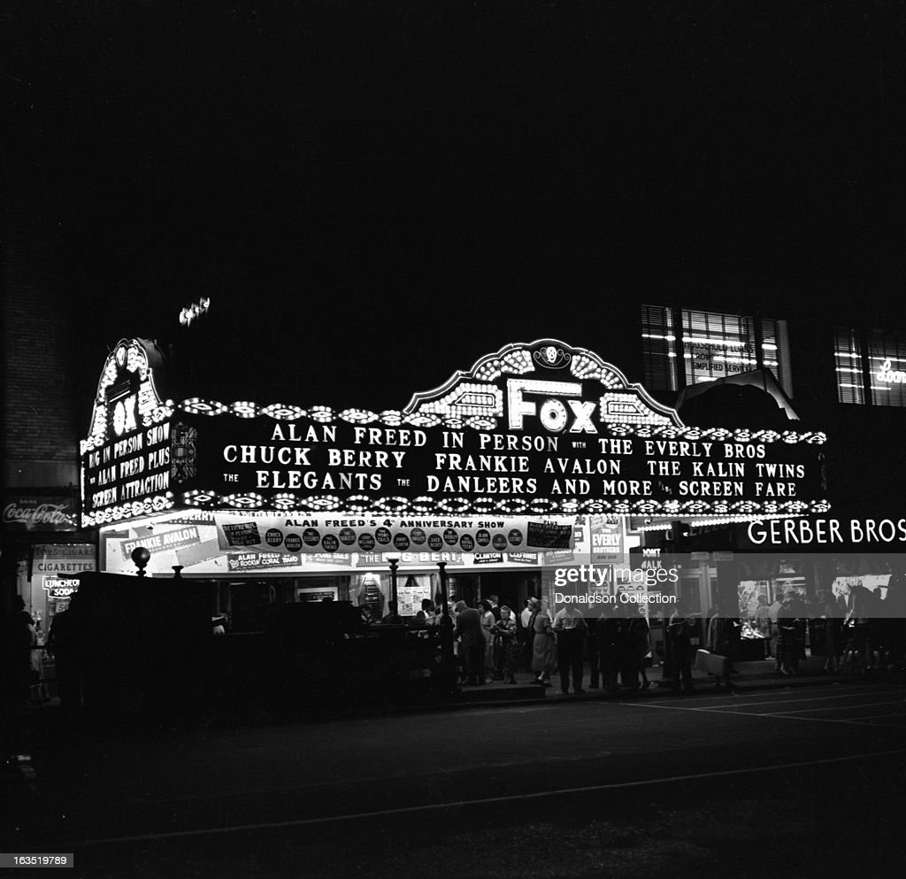 The marquee at the Brooklyn Fox Theater reads 'Alan Freed In Person, with The Everly Brothers, Chuck Berry, Frankie Avalon, The Kalin Twins, The Elegants, The Danleers and more plus screen fare' at Alan Freed's 4th anniversary show, 'The Big Beat' on August 29, 1958 at the Brooklyn Fox Theatre in New York, New York. An advertisement for Coca Cola is on the left. And the sign for Gerber Brothers is on the right.