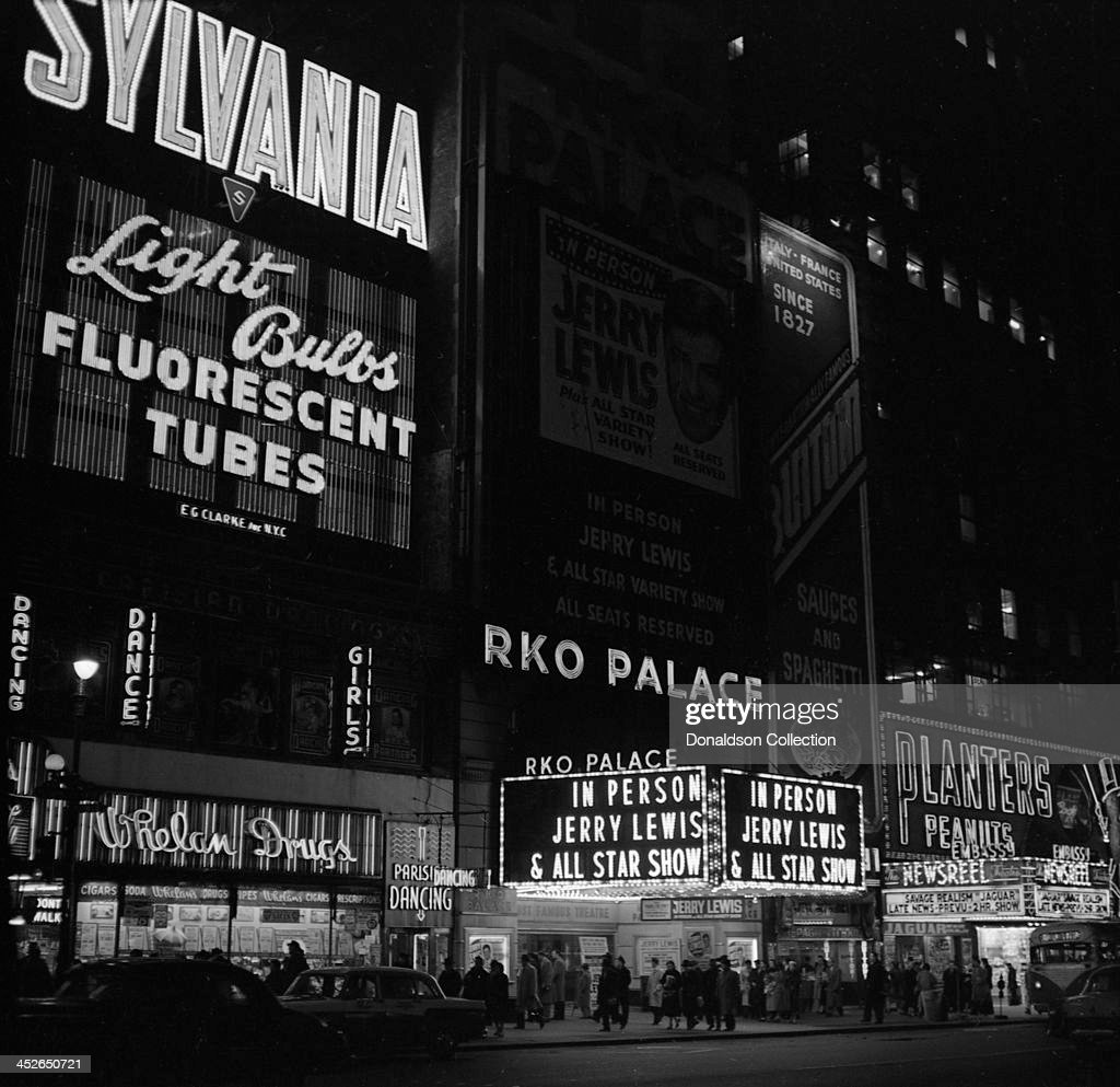 The Marquee reads 'In Person Jerry Lewis And All Star Variety Sjhow All Seats Reserved RKO Palace' for a Jerry Lewis show at the RKO Palace Theater with an advertisement for Sylvania Light Bulbs, Whelan Drugs store sign, Parisian Dancing sign, Buitoni Sauces and Spaghetti advertisement, Planters Peanuts advertisement on Broadway on February 7, 1957 in New York, New York.