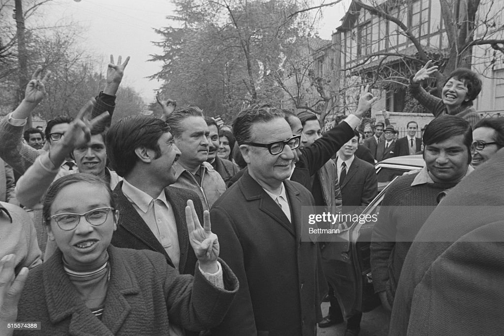 The Marxist candidate for the Chilean presidency Dr. <a gi-track='captionPersonalityLinkClicked' href=/galleries/search?phrase=Salvador+Allende&family=editorial&specificpeople=220786 ng-click='$event.stopPropagation()'>Salvador Allende</a> (center - with glasses) is surrounded by supporters as he arrives at a polling station, here, Sept. 4th. The supporters are waving three fingers to indicate Allende's place on the ballot.