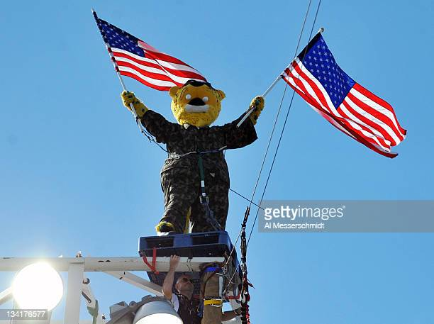 The mascot of the Jacksonville Jaguars stands above a light tower holding two American Flags during pregame cermonies November 27 2011 at EverBank...