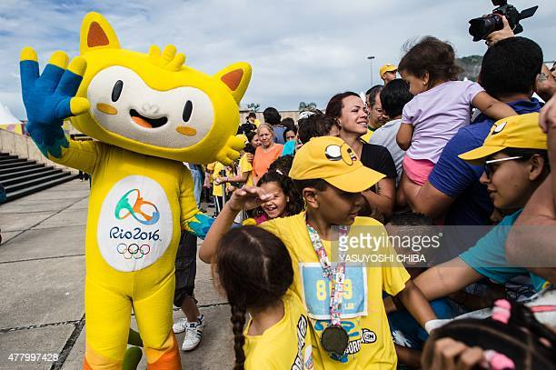 The mascot of the Rio 2016 Olympic Games Vinicius has its picture taken with fans during a family running race event by the Cartoon Network at...