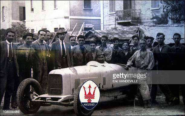 The Maserati brothers their employees and one of their sport cars in 1930
