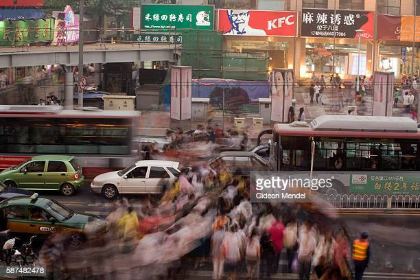 The massive number of pedestrians crossing busy intersection in the Xidan shopping area become a blur of movement as dusk falls during the Mayday...