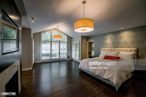 The master bedroom has designer wallpaper a woodpaneled fireplace and floortoceiling windows that offer views of the backyard and its swimming pool