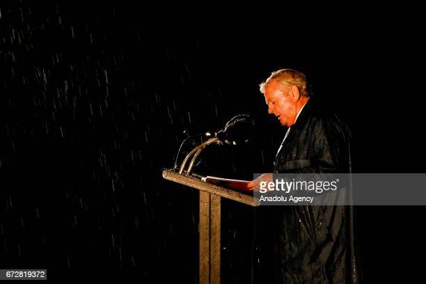 The master of ceremonies addresses the crowd in the rain during the dawn service of the ANZAC day commemoration at the Shrine of Remembrance in...