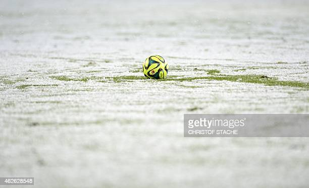 The match ball lays between snow during the German first division Bundesliga football match FC Augsburg v 1899 Hoffenheim at SGL Arena in Augsburg...