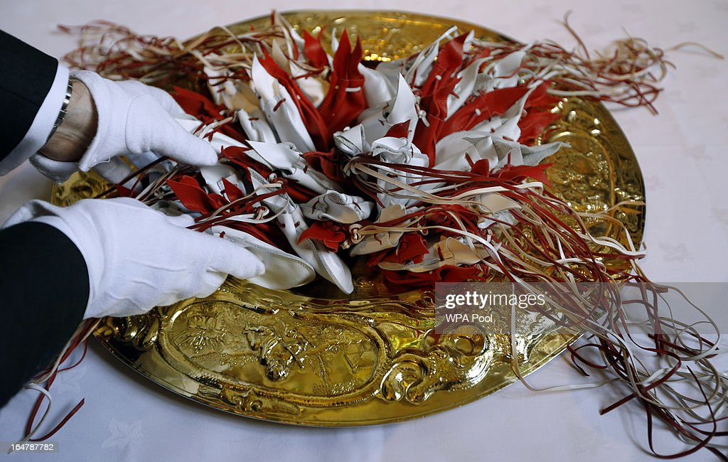 The Maundy purses are arranged on a gold plate ready for distribution by Queen Elizabeth II during the Maundy service, at Christ Church Cathedral on March 28, 2013 in Oxford, England. The Maundy money was today distributed by the Queen to 87 women and 87 men, who each received two purses, one red and one white. A 5 GBP coin and 50 pence coin commemorating the 60th anniversary of The Queen's Coronation in the red purse. The white purse contains the uniquely minted Maundy Money. This takes the form of silver one, two, three and four penny pieces, the sum of which equals the number of years the Monarch's age.
