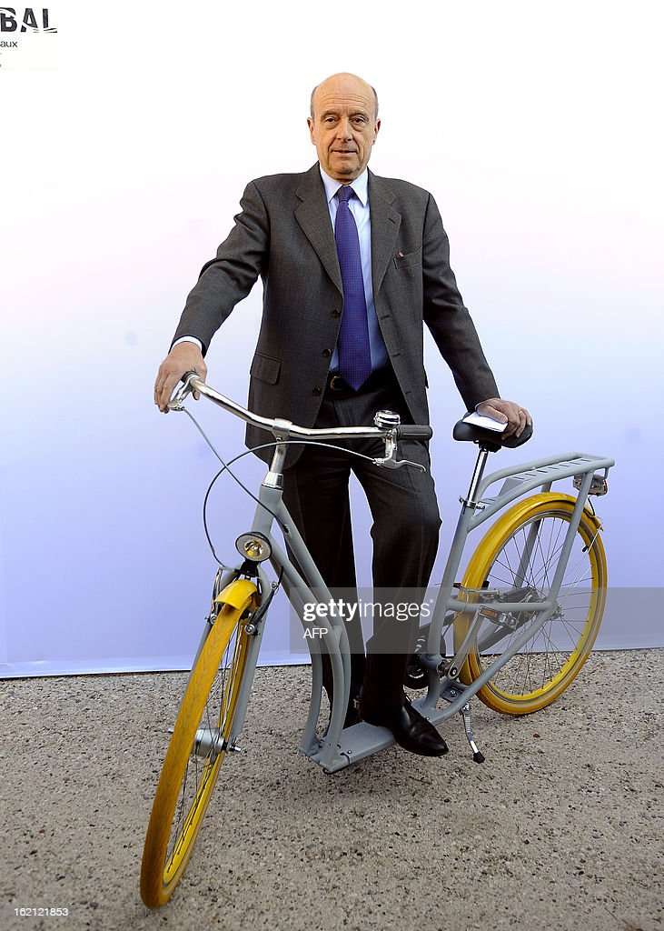 The Mayor of Bordeaux Alain Juppe poses on February 19, 2013 with 'the Pibal', the city's new hybrid urban bicycle designed by Philippe Starck during the unveiling at the Town Hall. The bikes, manufactured by Peugeot, should be available in September 2013.