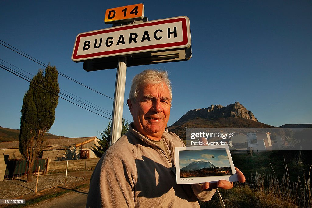 The mayor of Bugarach, Jean Pierre Delord, poses with a postcard showing 'Ufo' in front of the village. Some are claiming the village of Bugarach will be the only surviving settlement following a devastating apocalypse in December 2012, on November 24, 2011 in Bugarach, France. Although free publicity has boosted the housing market in the village, the Mayor is concerned about the worldwide publicity and the increased volume of people it might attract to the village and it's mountain, Pic de Bugarach.