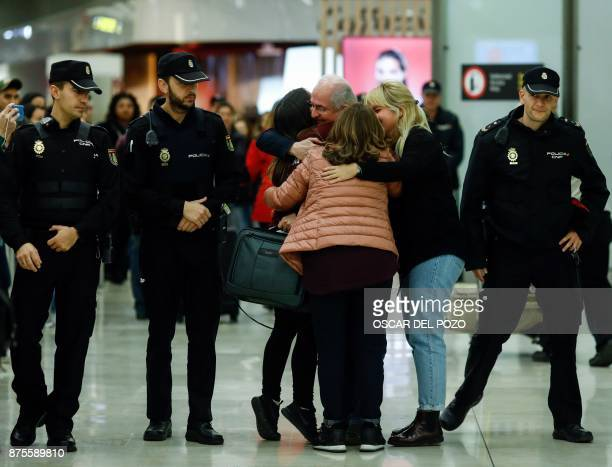 TOPSHOT The mayor of Caracas Antonio Ledezma hugs his wife Mtzy Capriles and his daughter Antoneta upon his arrival to the Barajas Airport on...