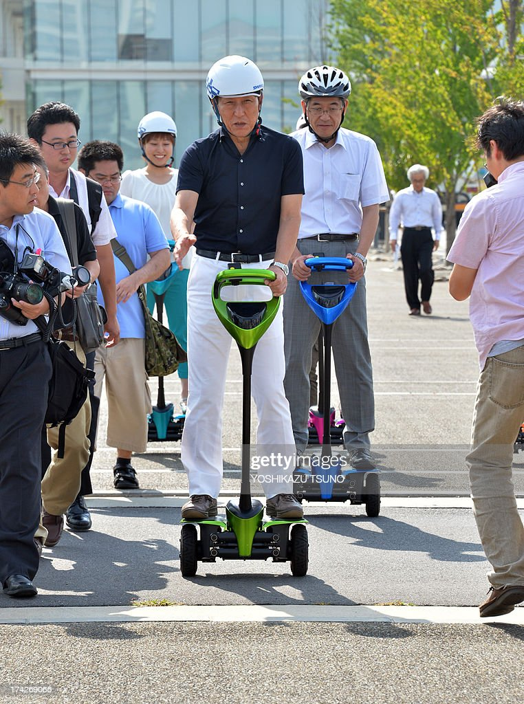 The mayor of Japan's Tsukuba City, Kenichi Ichihara (C), and Toyota Motor partner robot director Akifumi Tamaoki (centre R-white shirt) ride on Toyota's transport assistance robot, called the 'Winglet', on a public sidewalk in Tsukuba City, suburban Tokyo on July 23, 2013. Toyota and Tsukuba City started to field test the next generation of 'personal mobility robot' on the public thoroughfare, with trial runs scheduled until 2016. AFP PHOTO / Yoshikazu TSUNO
