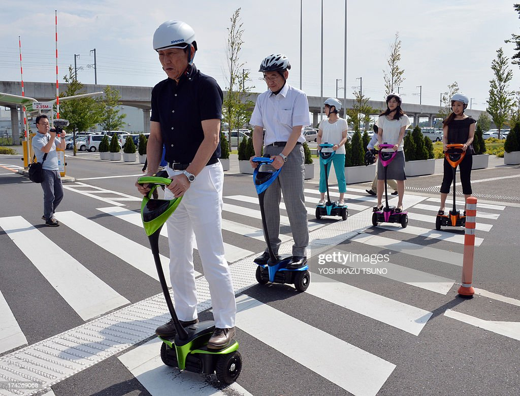 The mayor of Japan's Tsukuba City, Kenichi Ichihara (front L), and Toyota Motor partner robot director Akifumi Tamaoki (2nd L) ride with city hall employees on Toyota's transport assistance robot, called the 'Winglet', as they cross a road in Tsukuba City, suburban Tokyo on July 23, 2013. Toyota and Tsukuba City started to field test the next generation of 'personal mobility robot' on the public thoroughfare, with trial runs scheduled until 2016. AFP PHOTO / Yoshikazu TSUNO