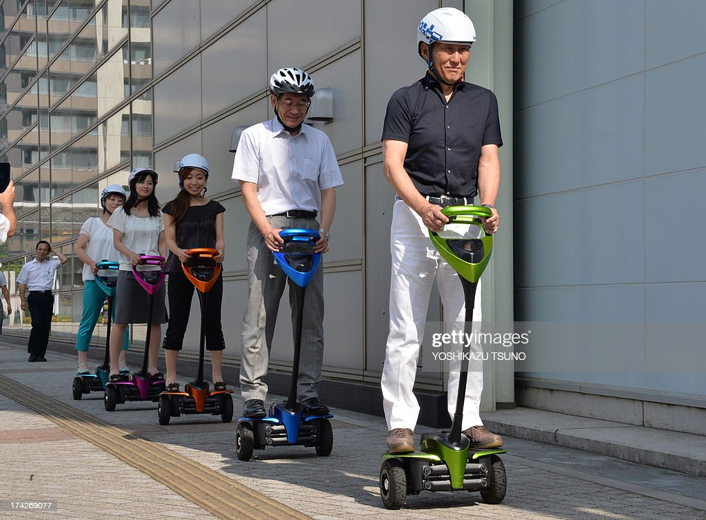 The mayor of Japan's Tsukuba City, Kenichi Ichihara (R), and Toyota Motor partner robot director Akifumi Tamaoki (2nd R) ride with city hall employees on Toyota's transport assistance robot, called the 'Winglet', on a public sidewalk in Tsukuba City, suburban Tokyo on July 23, 2013. Toyota and Tsukuba City started to field test the next generation of 'personal mobility robot' on the public thoroughfare, with trial runs scheduled until 2016. AFP PHOTO / Yoshikazu TSUNO