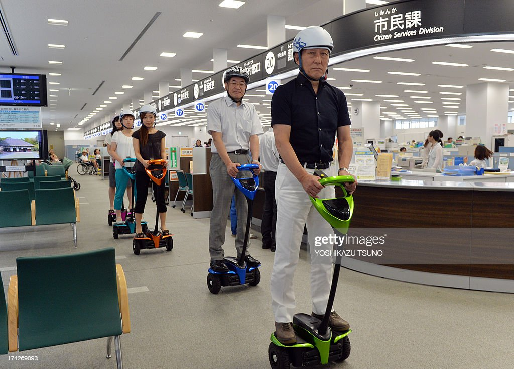 The mayor of Japan's Tsukuba City, Kenichi Ichihara (R), and Toyota Motor partner robot director Akifumi Tamaoki (2nd R) ride with city hall employees on Toyota's transport assistance robot, called the 'Winglet', at City Hall in Tsukuba City, suburban Tokyo on July 23, 2013. Toyota and Tsukuba City started to field test the next generation of 'personal mobility robot' on the public thoroughfare, with trial runs scheduled until 2016. AFP PHOTO / Yoshikazu TSUNO