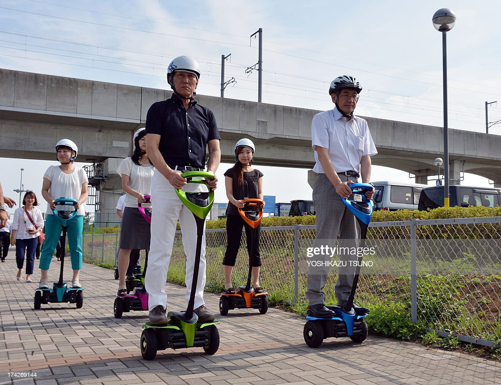 The mayor of Japan's Tsukuba City, Kenichi Ichihara (C), and Toyota Motor partner robot director Akifumi Tamaoki (R) ride with city hall employees on Toyota's transport assistance robot, called the 'Winglet', on a public sidewalk in Tsukuba City, suburban Tokyo on July 23, 2013. Toyota and Tsukuba City started to field test the next generation of 'personal mobility robot' on the public thoroughfare, with trial runs scheduled until 2016. AFP PHOTO / Yoshikazu TSUNO