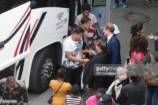The Mayor of Montreal Denis Coderre greets a bus of Haitian asylum seekers from the United States as it arrives at the Olympic Stadium in Montreal...