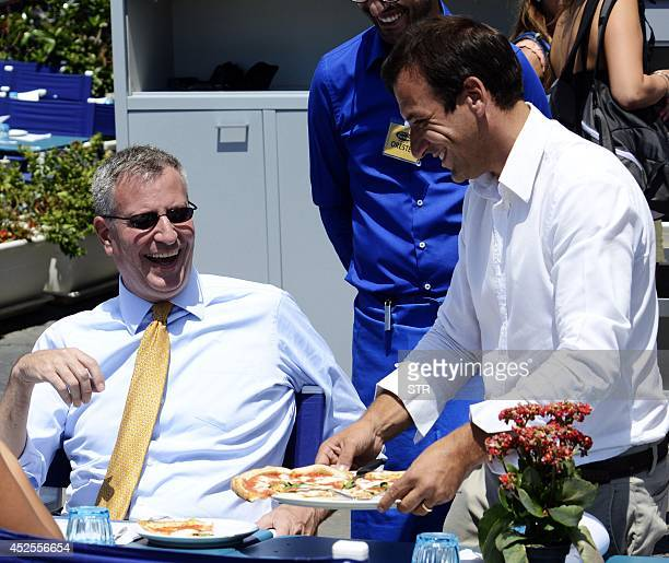 The mayor of New York city mayor Bill de Blasio laughs while talking to a waiter at a pizzeria in Naples southern Italy on July 23 2014 De Blasio is...