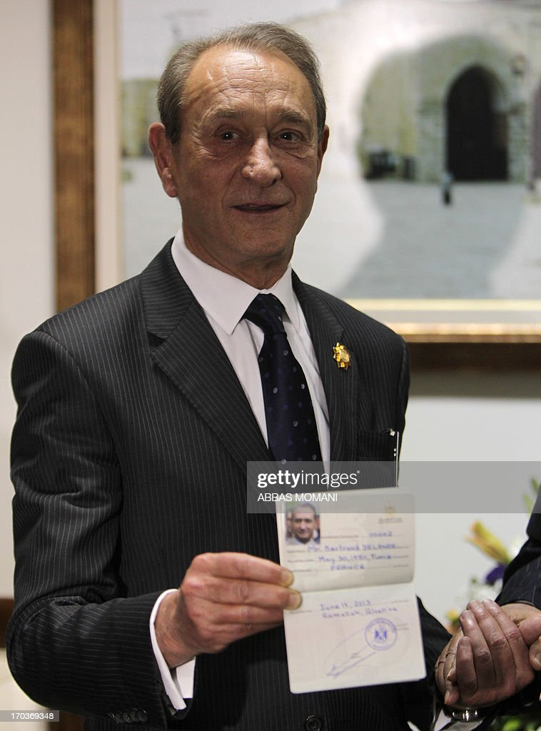 The Mayor of Paris, Bertrand Delanoë, shows off his Palestinian honorary citizenship bestowed on him by Palestinian president Mahmud Abbas (unseen) during his visit to the West Bank city of Ramallah on June 12, 2013.