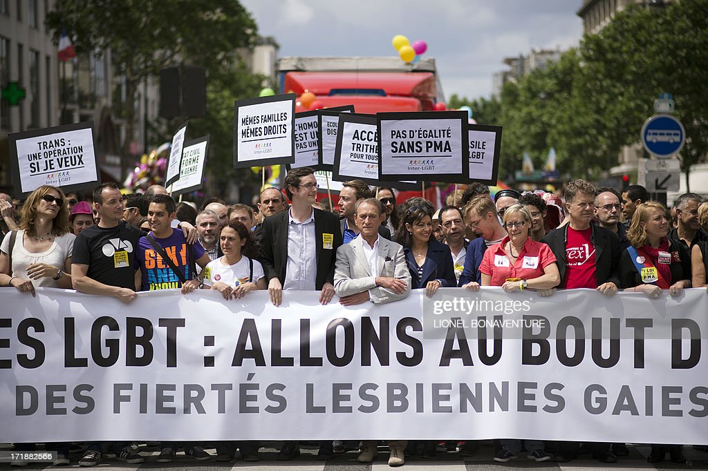The Mayor of Paris Bertrand Delanoe (C) next to deputy mayor and socialist candidate to the 2014 municipal elections in Paris Anne Hidalgo take part in the homosexual, lesbian, bisexual and transgender (HLBT) visibility march, the Gay Pride, on June 29, 2013 in Paris. AFP PHOTO / LIONEL BONAVENTURE