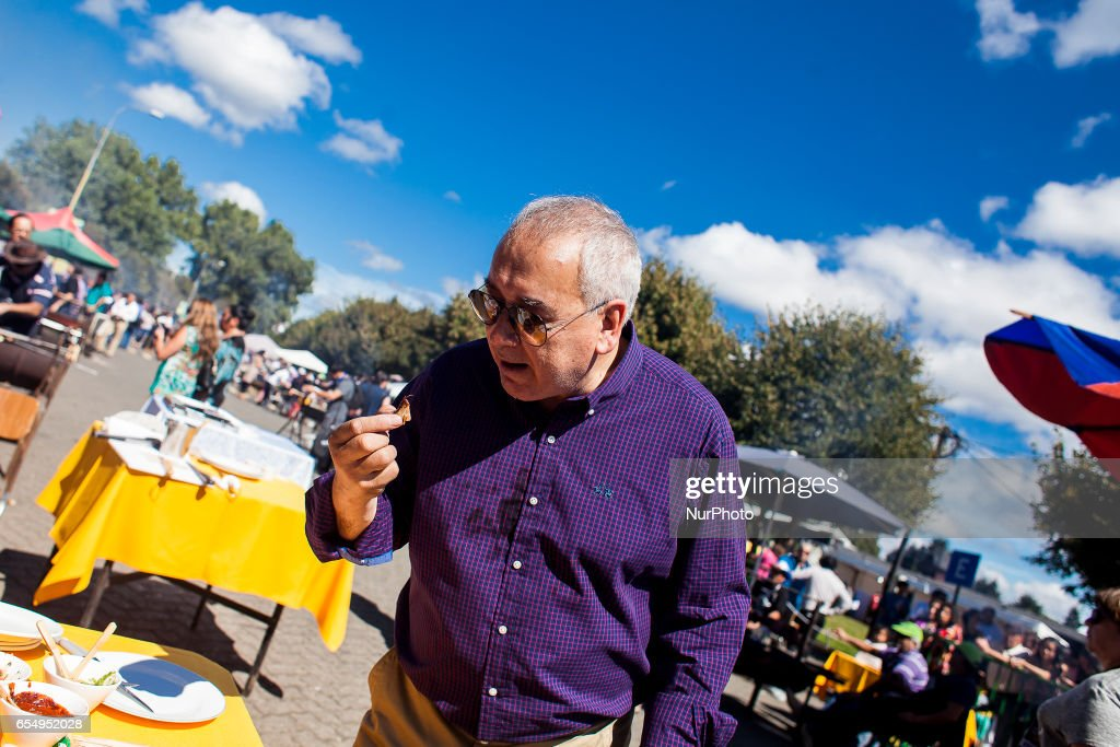 The mayor of the city of Orono Claudio Bertin eats a piece of roast beef. More than one hundred people participated in the roasting contest organized by the City of Osorno, Chile, on 18 March 2017 that was held in Chuyaca Park, this activity seeks to highlight the important meat production in the region.