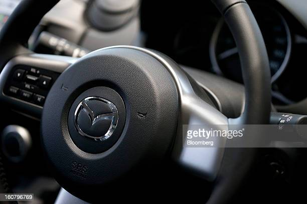 The Mazda Motor Corp logo is displayed on the steering wheel of a Demio compact vehicle at the company's showroom in Tokyo Japan on Wednesday Feb 6...
