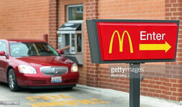 The McDonald's Corp logo is displayed on a sign as a customer receives an order at the driveup window of a restaurant in Chicago Illinois US on...