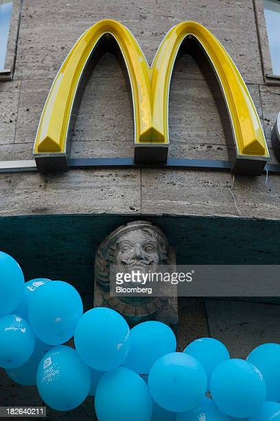 The McDonald's Corp logo sits displayed above balloons outside of a restaurant in Dusseldorf Germany on Tuesday Oct 1 2013 The Bundesbank said last...