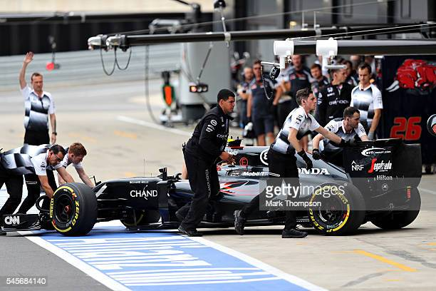 The Mclaren team push Jenson Button of Great Britain and McLaren Honda back into the garage during qualifying for the Formula One Grand Prix of Great...