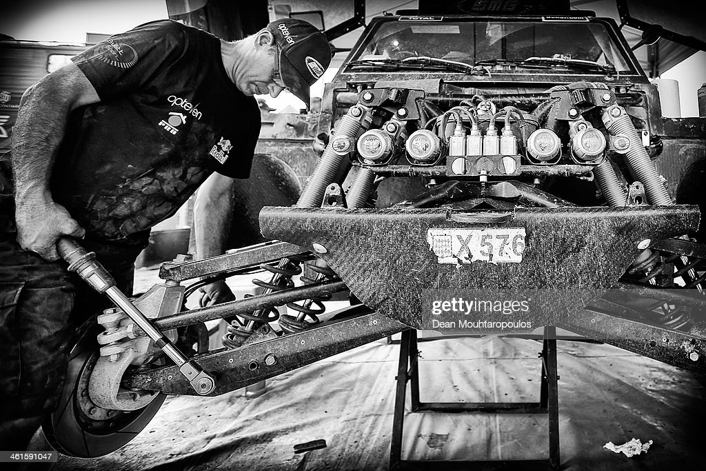 The mechanics work on car (#303) for Carlos Sainz of Spain for the SMG Buggy and Red Bull Rally Team during Day 4 of the 2014 Dakar Rally on January 8, 2014 in Chilecito, Argentina.
