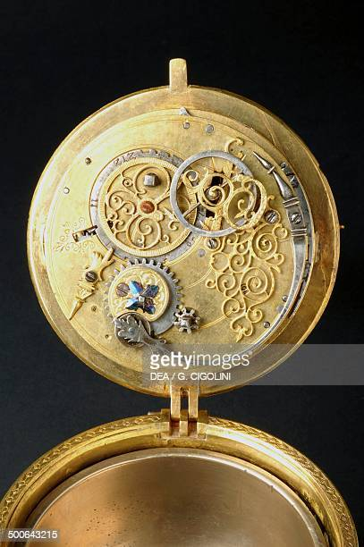The mechanism of a crucifixshaped gilt brass clock with cast moulded figures rocker arm mechanism on which is mounted a springloaded cam mechanism...
