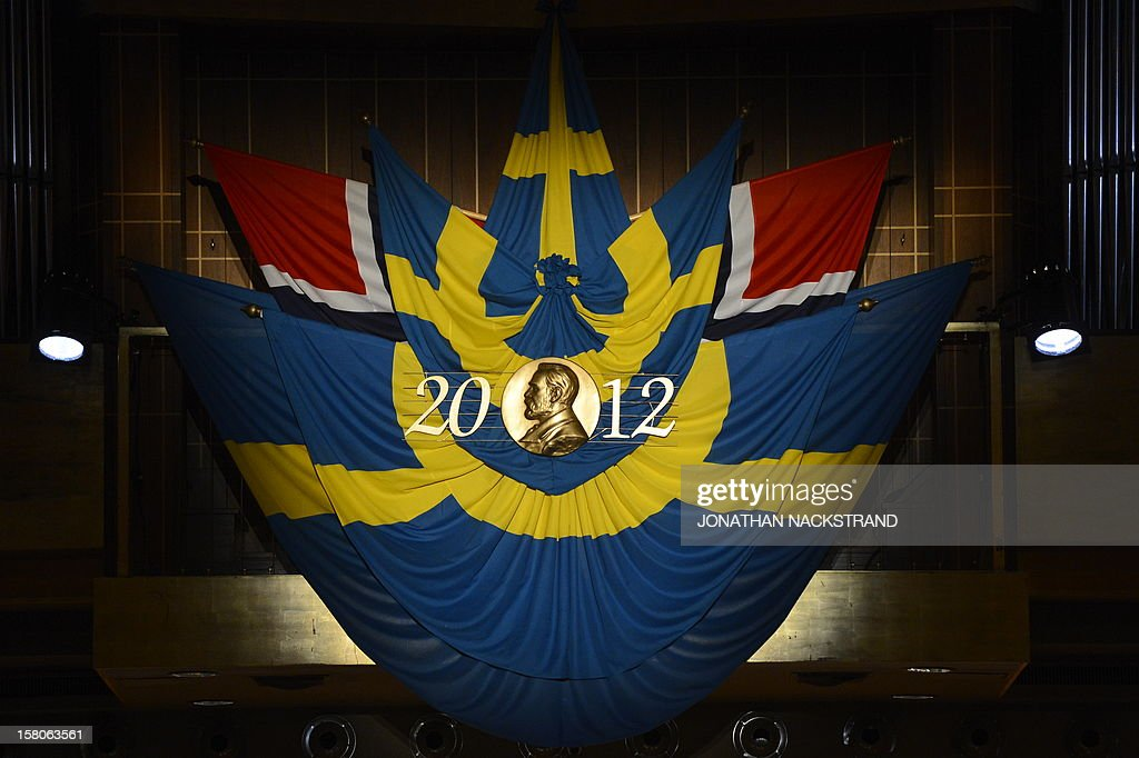 The medal of Alfred Nobel and Swedish flags are seen prior to the Nobel prize awarding ceremony at the Stockholm Concert Hall on December 10, 2012 in Stockholm, Sweden. The winners of the Nobel Prize 2012 in the categories of medicine, physics, chemistry, literature and economics receive their awards from the hands of Sweden's King Carl XVI Gustaf at a formal ceremony, followed by a gala banquet. AFP PHOTO / SCANPIX-SWEDEN / HENRIK MONTGOMERY / SWEDEN OUT