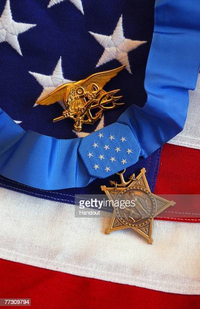 The Medal of Honor rests on a flag beside a SEAL trident during preparations for an award ceremony for Lt Michael P Murphy October 2 2007 in...